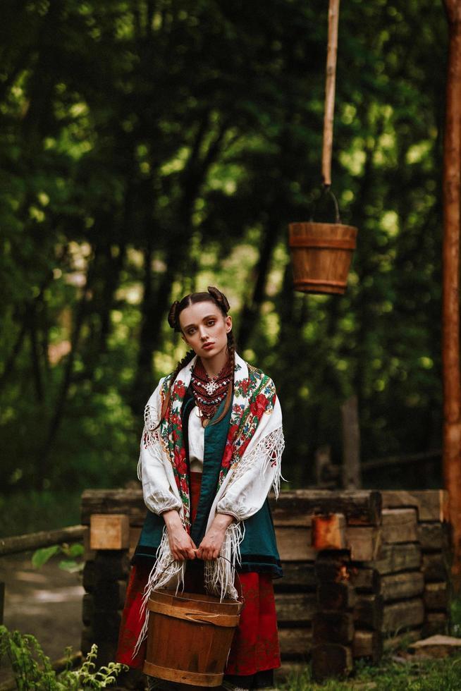 junges Mädchen in einem ukrainischen Kleid posiert mit einem Eimer in der Nähe des Brunnens foto