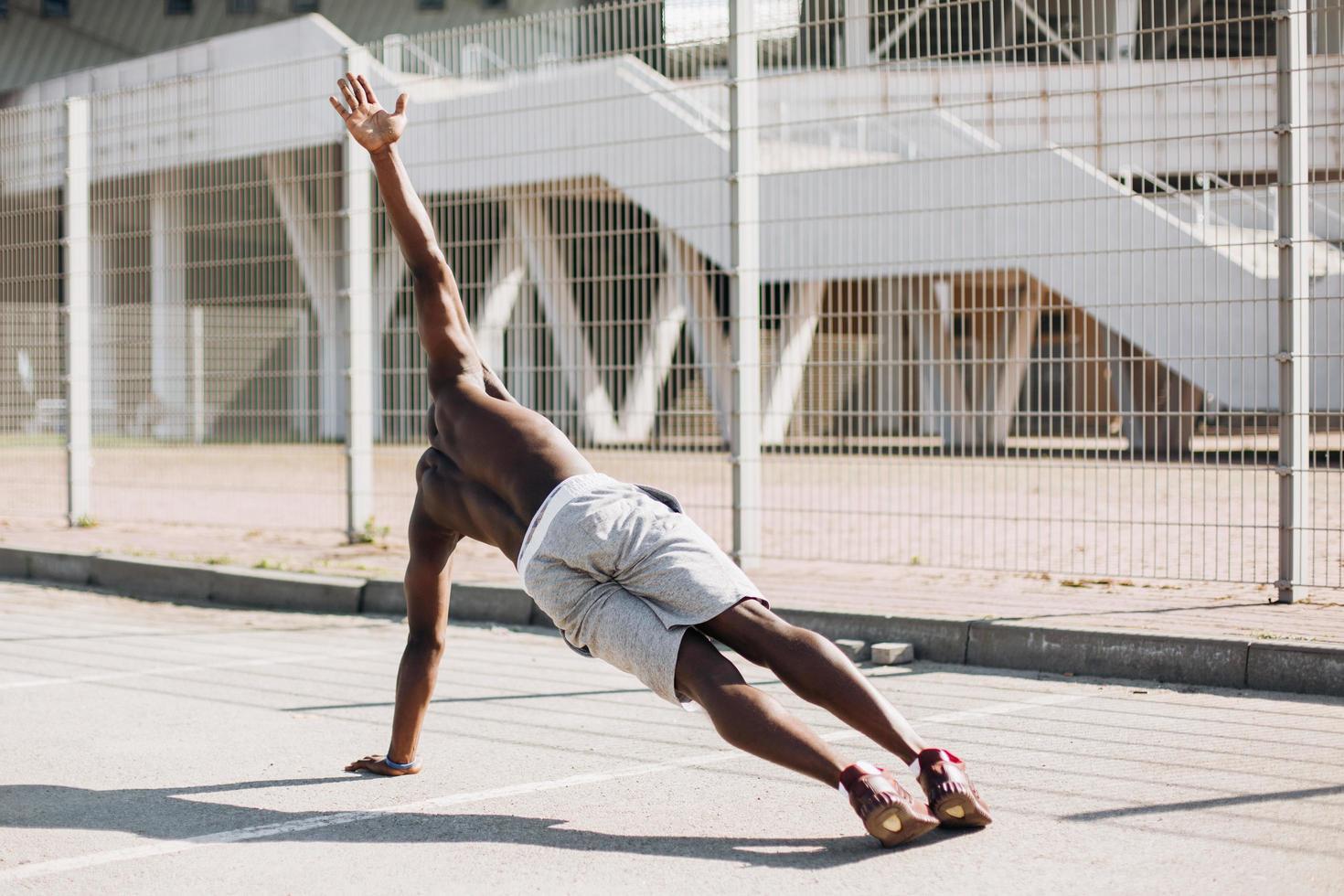 Afroamerikanermann, der Seitenplanke tut foto