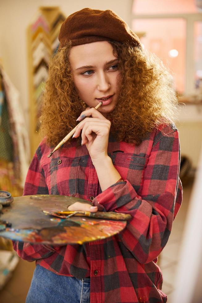 Künstlerin hält einen Pinsel und denkt über ihre Arbeit nach foto