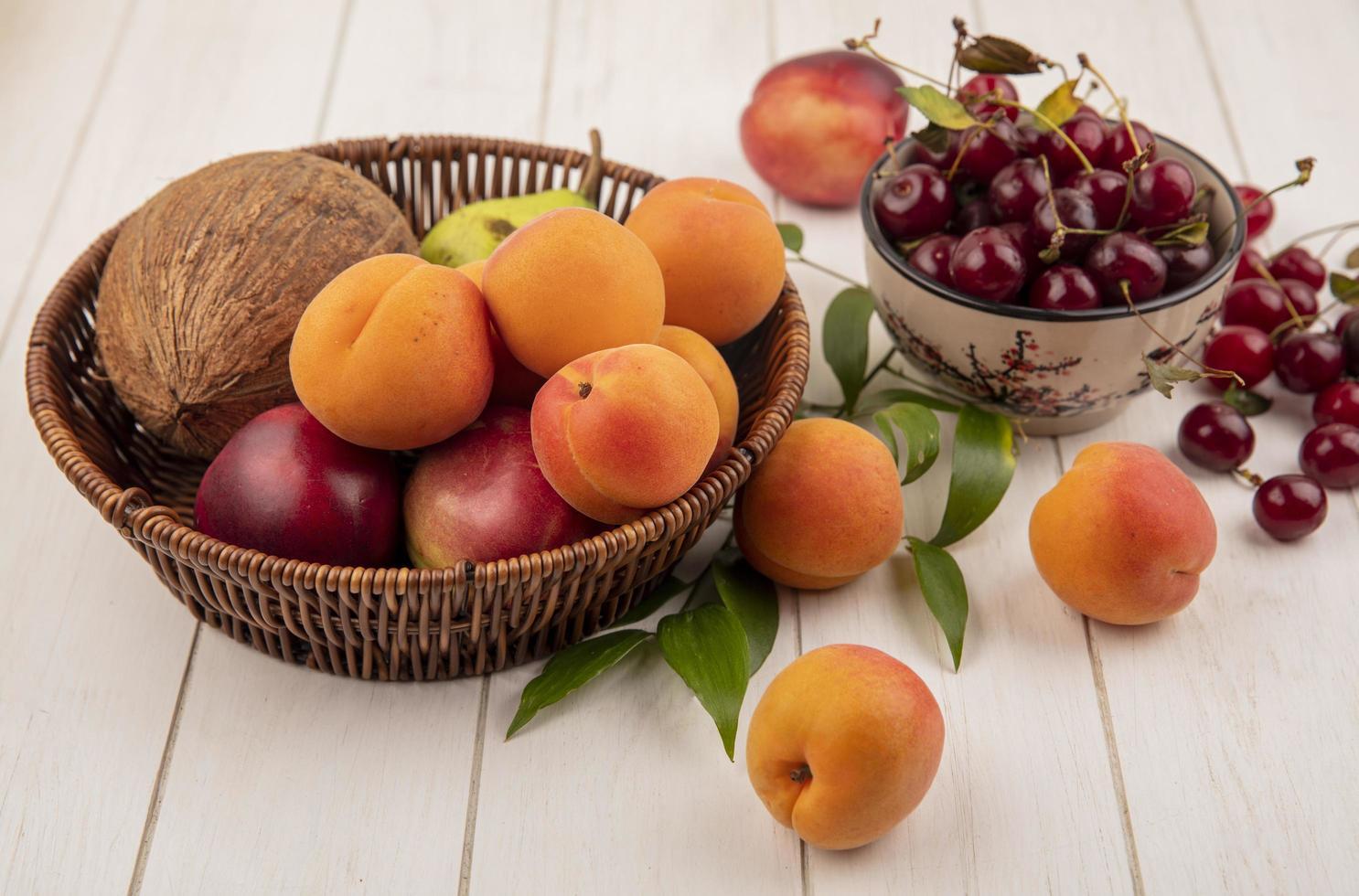 verschiedene Früchte in einem Korb auf Holzoberfläche foto