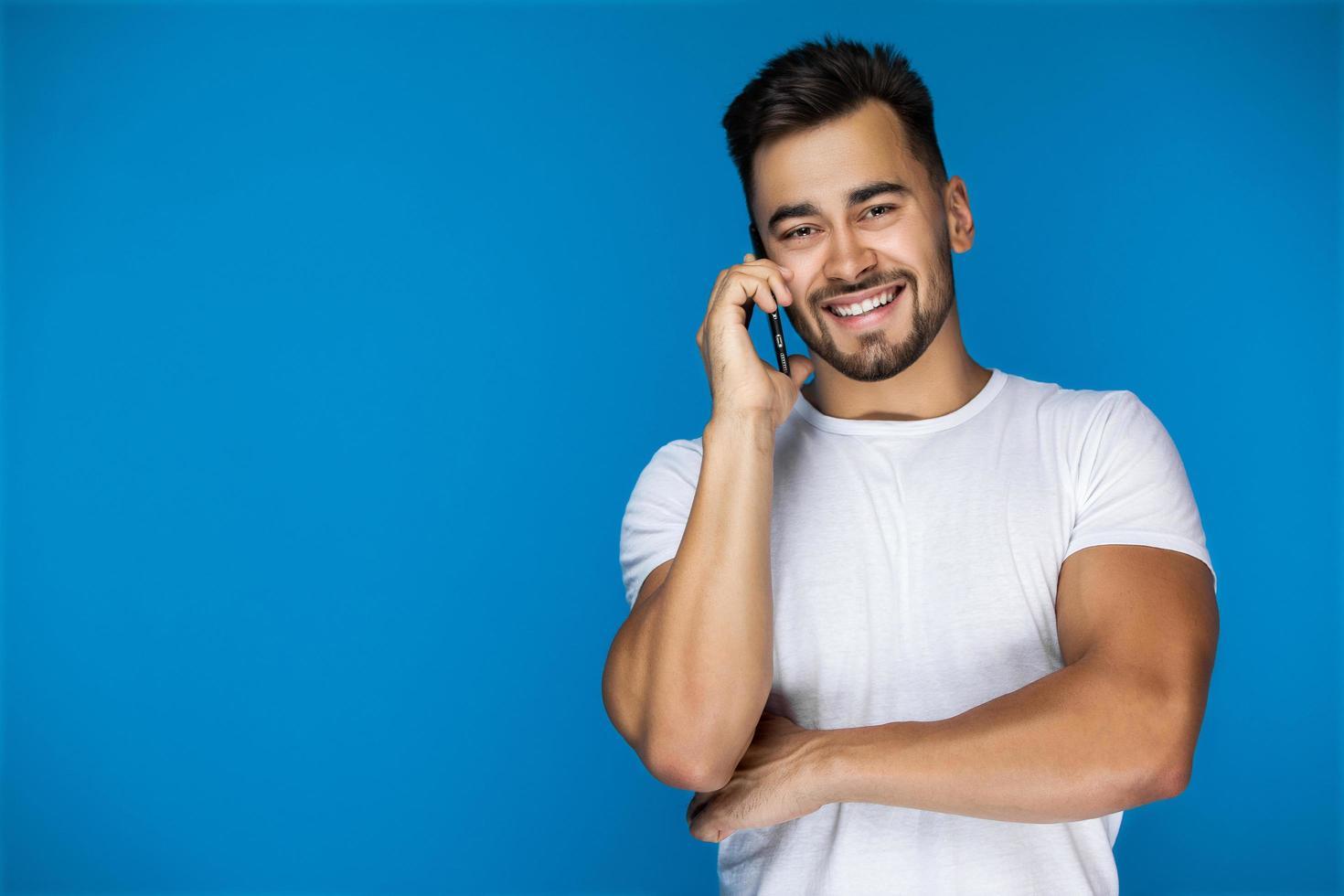 Mann lächelt, während am Telefon foto