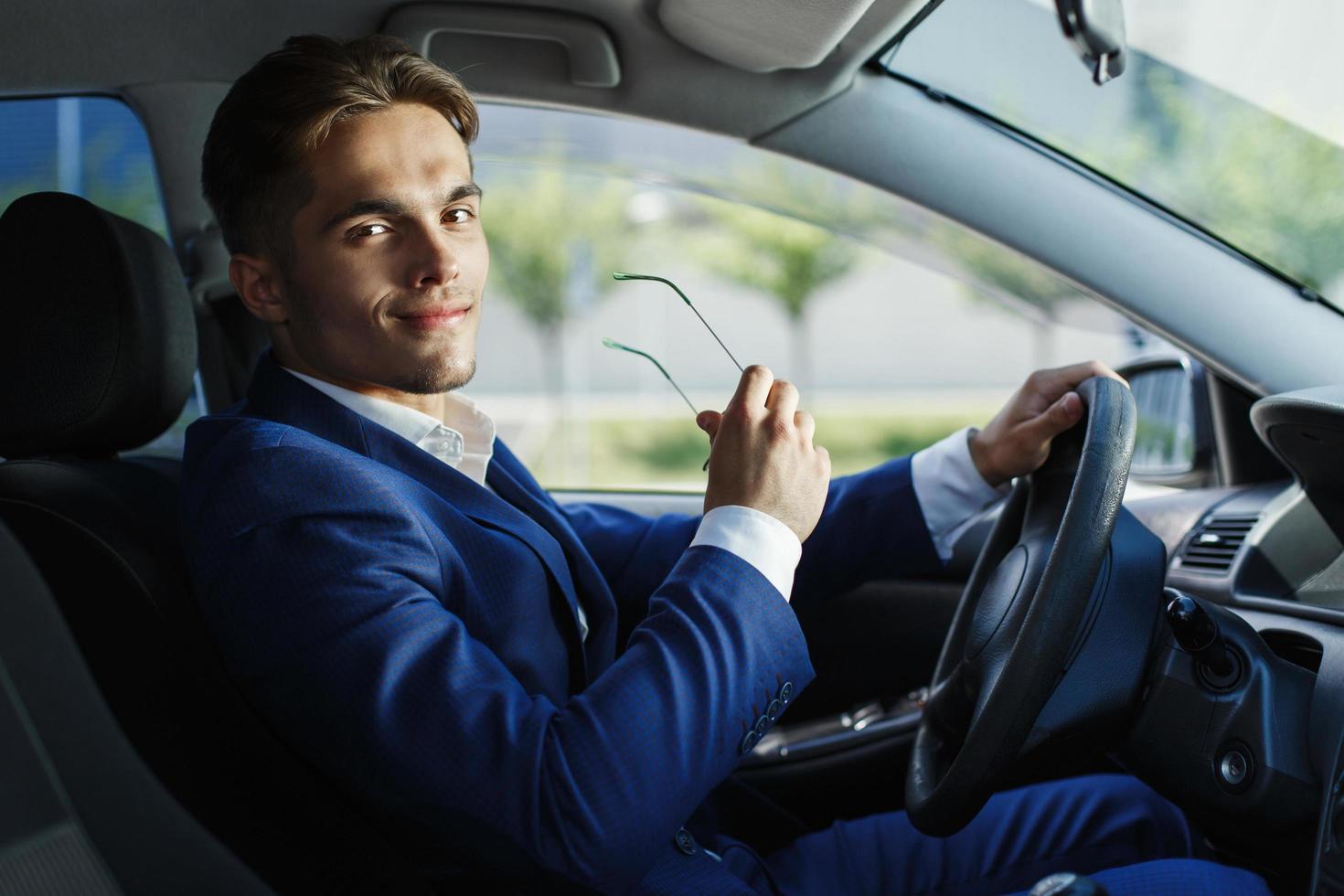 hübscher junger Geschäftsmann sitzt am Lenkrad im Auto foto