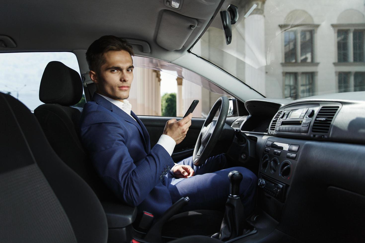 Der lächelnde Geschäftsmann sitzt im Auto und arbeitet mit seinem Smartphone foto