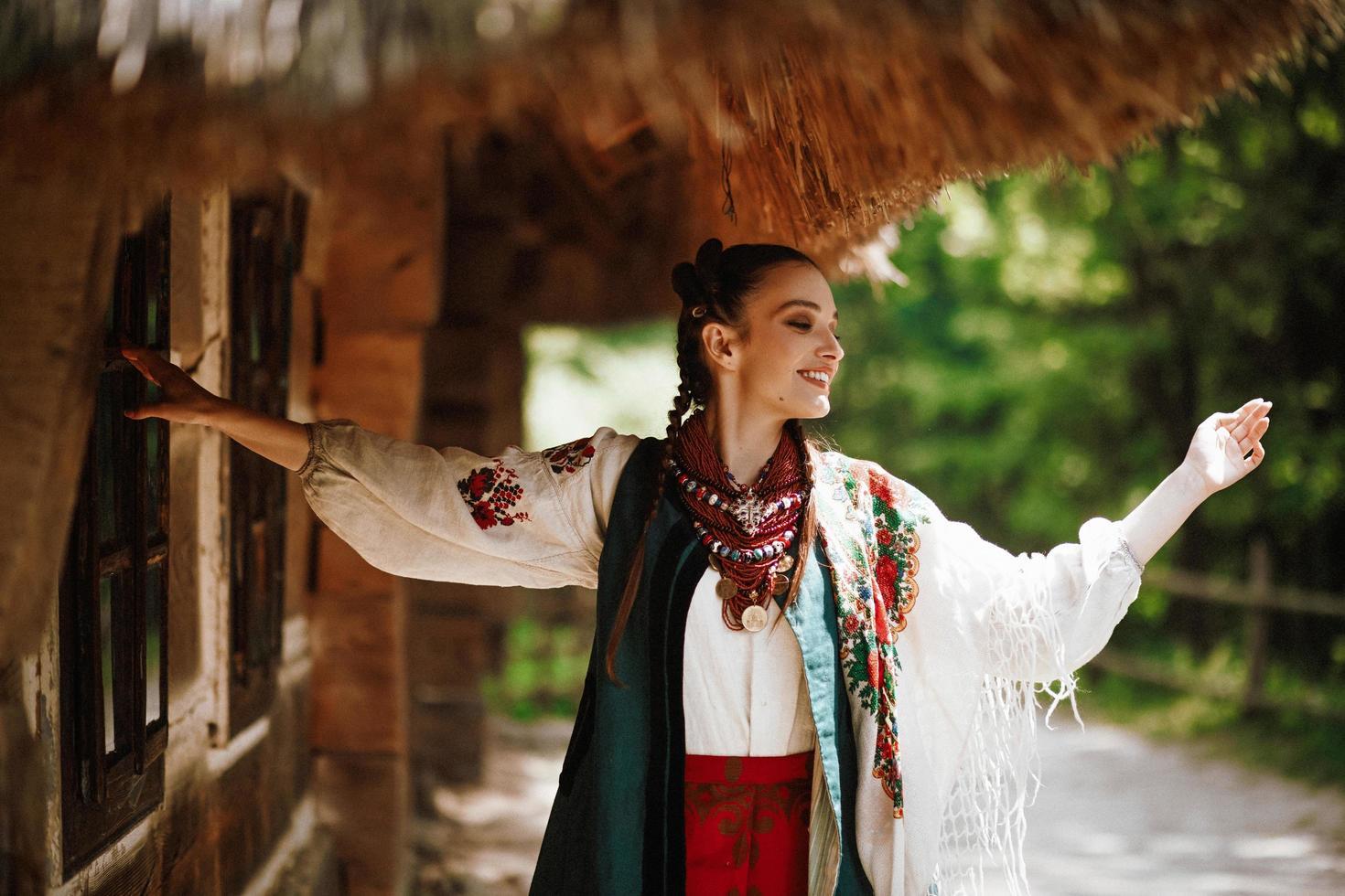 schönes Mädchen in einem traditionellen ukrainischen Kleid tanzt und lächelt foto