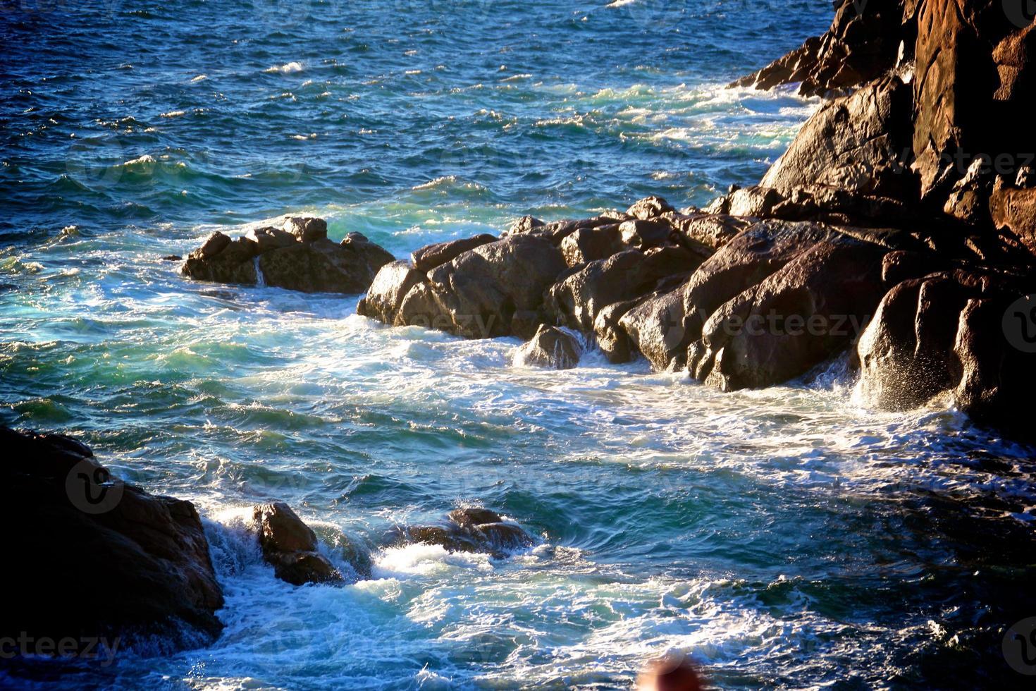 Wellen krachen gegen Felsen foto