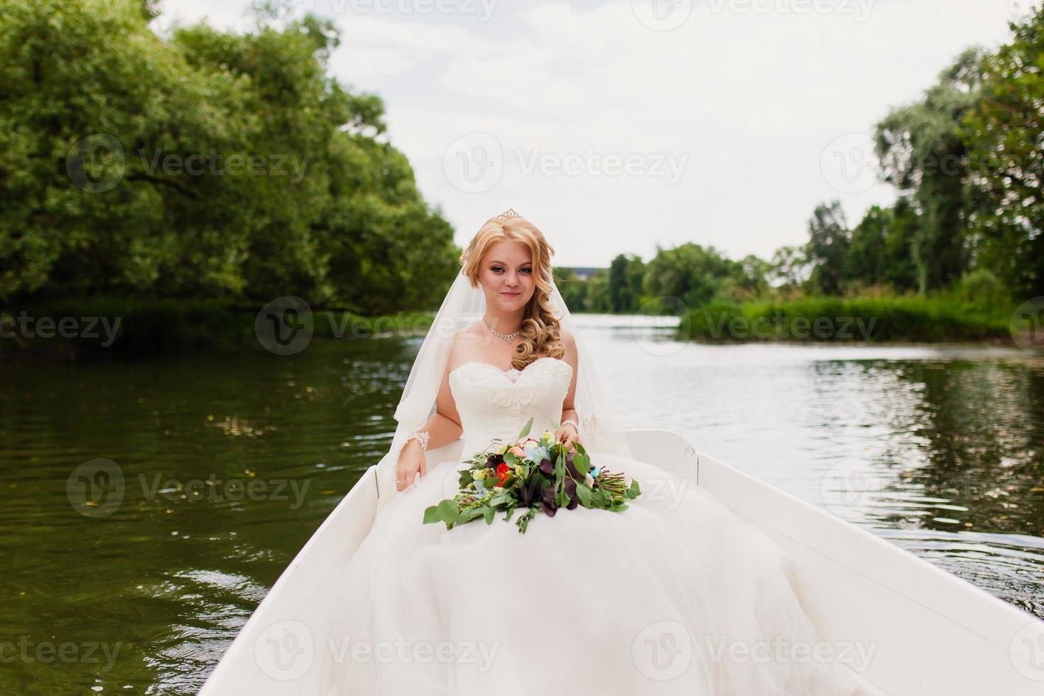 Braut in einem weißen Boot auf dem See foto