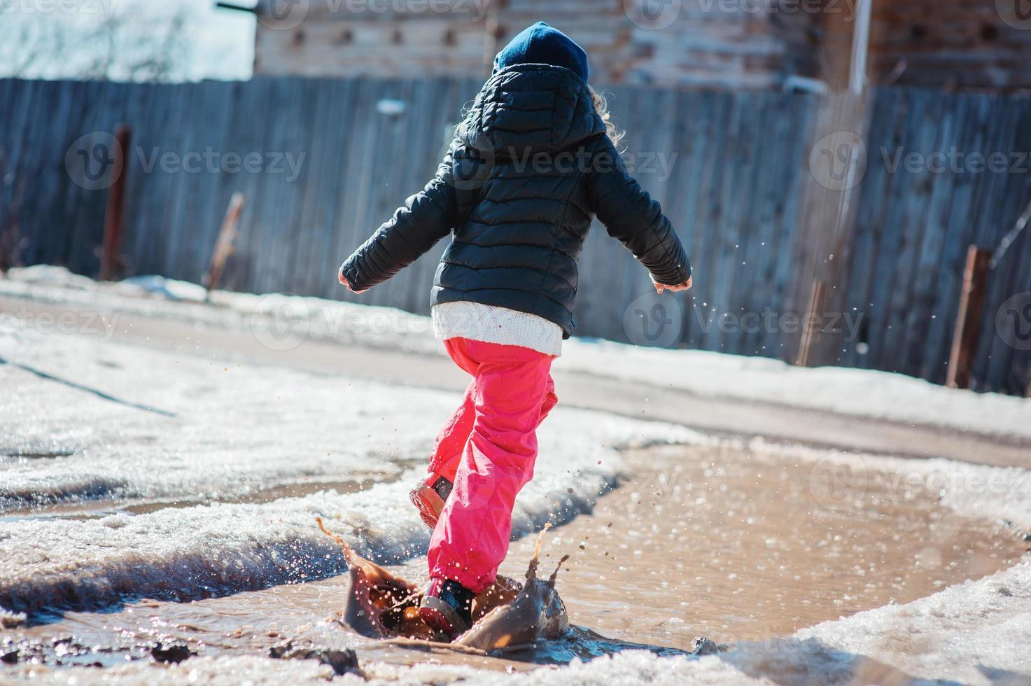 Kindermädchen spielt Pfützenspringen auf Frühlingsspaziergang, Aktivitäten im Freien foto