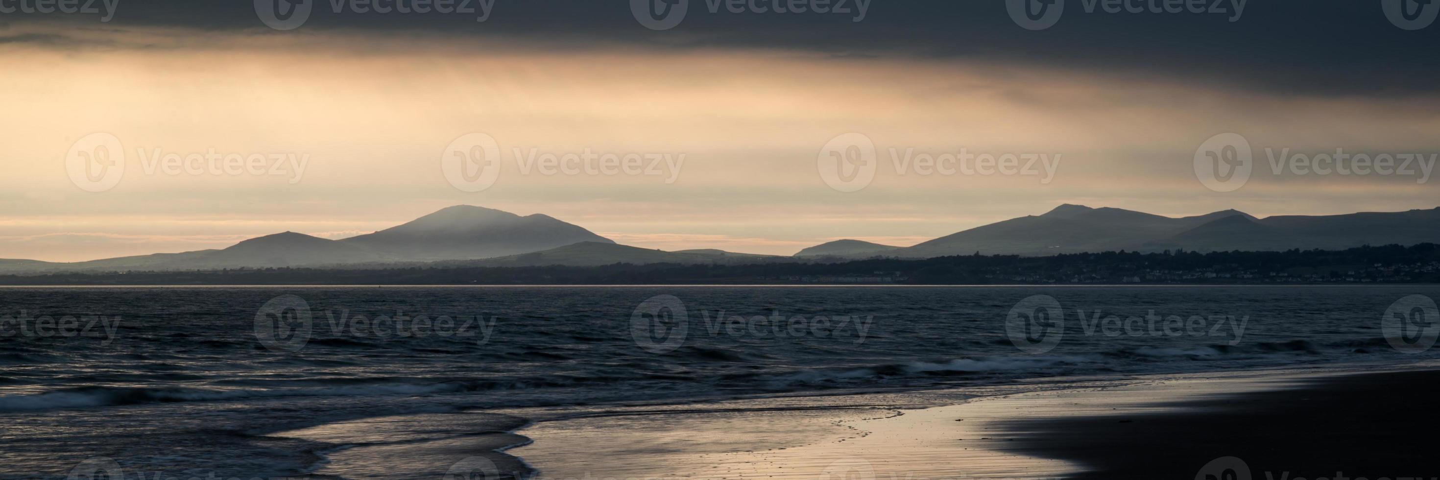 Panoramalandschaft atemberaubende Bergkette und Strand bei lebendigem Sonnenuntergang foto