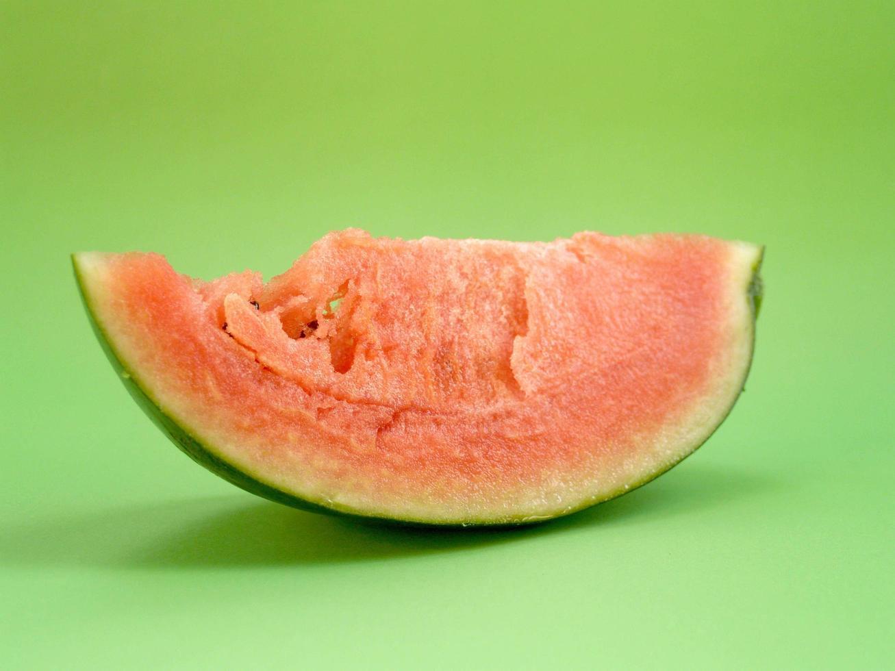 Wassermelonenscheibe auf grünem Hintergrund foto