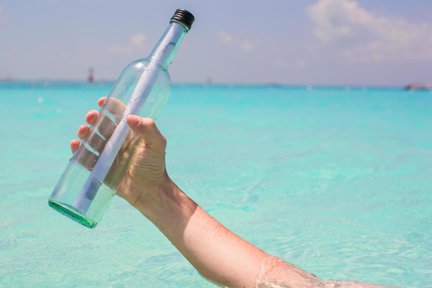 Person, die eine Glasflasche mit einer Nachricht darin hält foto