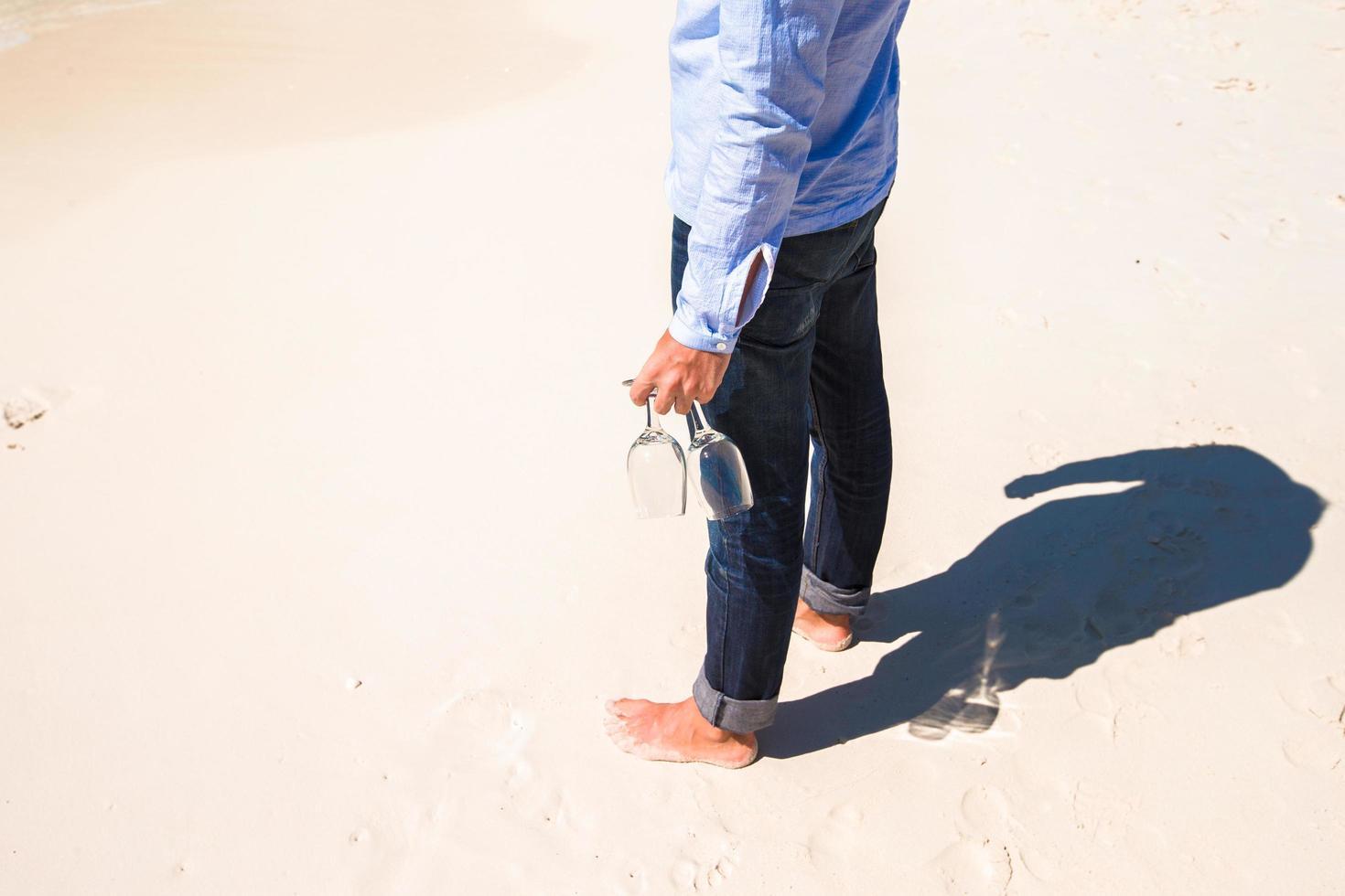 Mann hält Weingläser an einem Strand foto