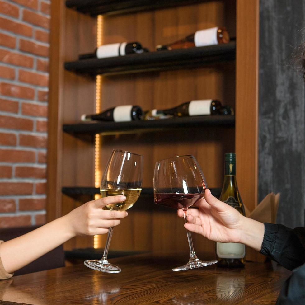 Frauen klirren an der Bar mit Weingläsern foto