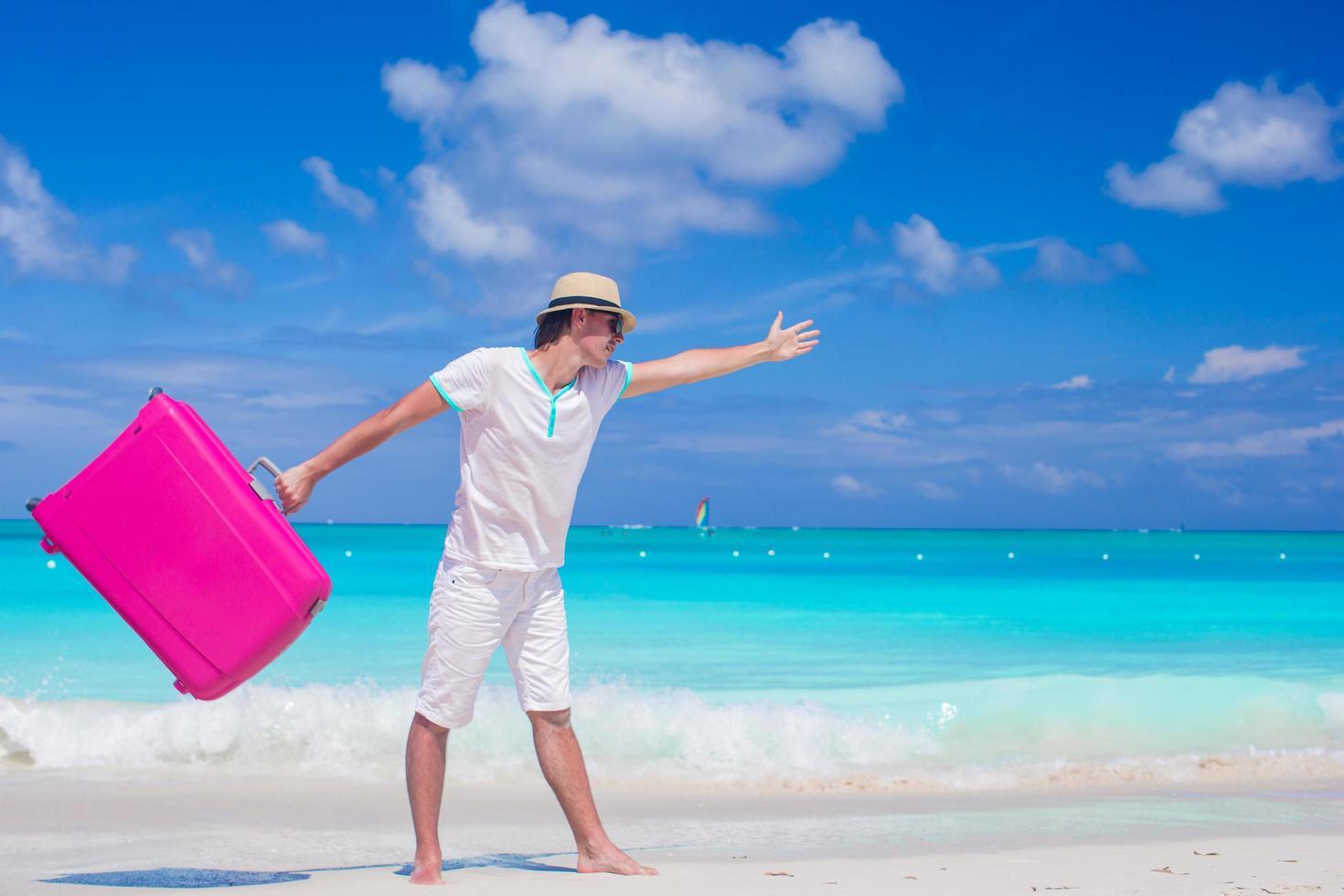 Mann, der mit einem Koffer auf einem Strand geht foto