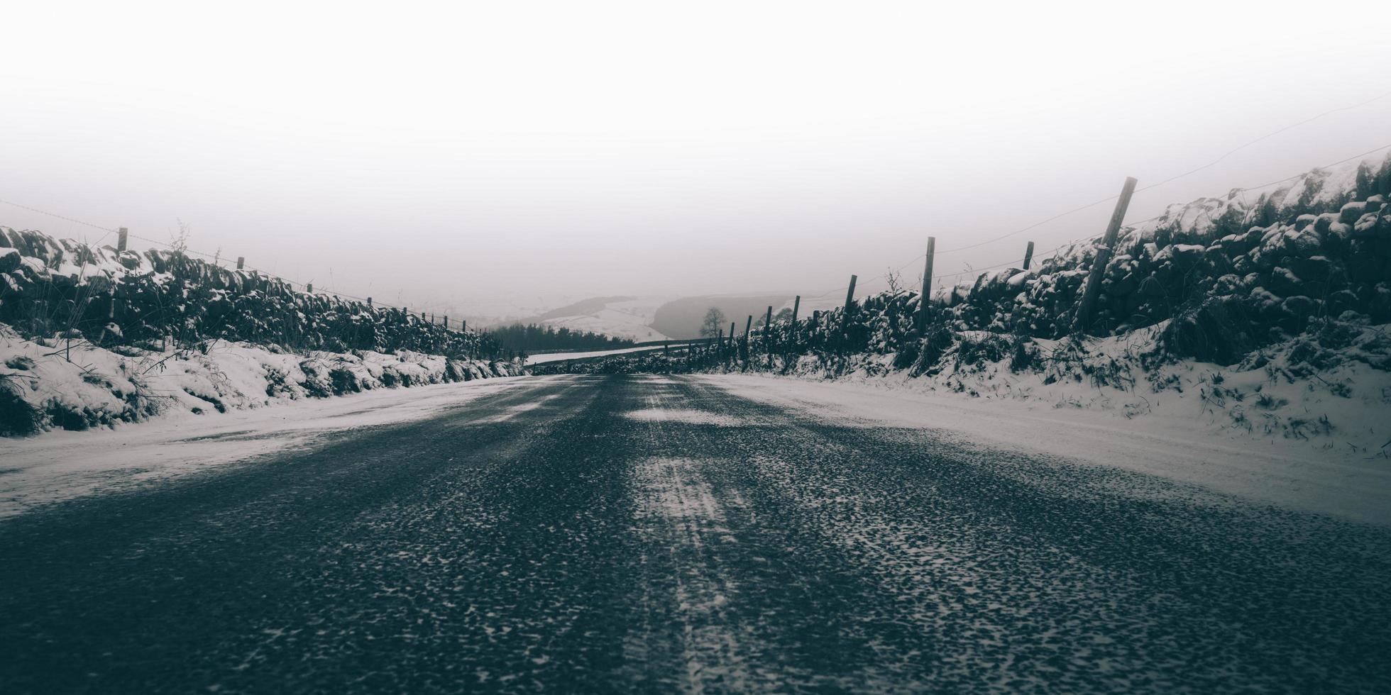 Graustufen einer von Schnee umgebenen Straße foto