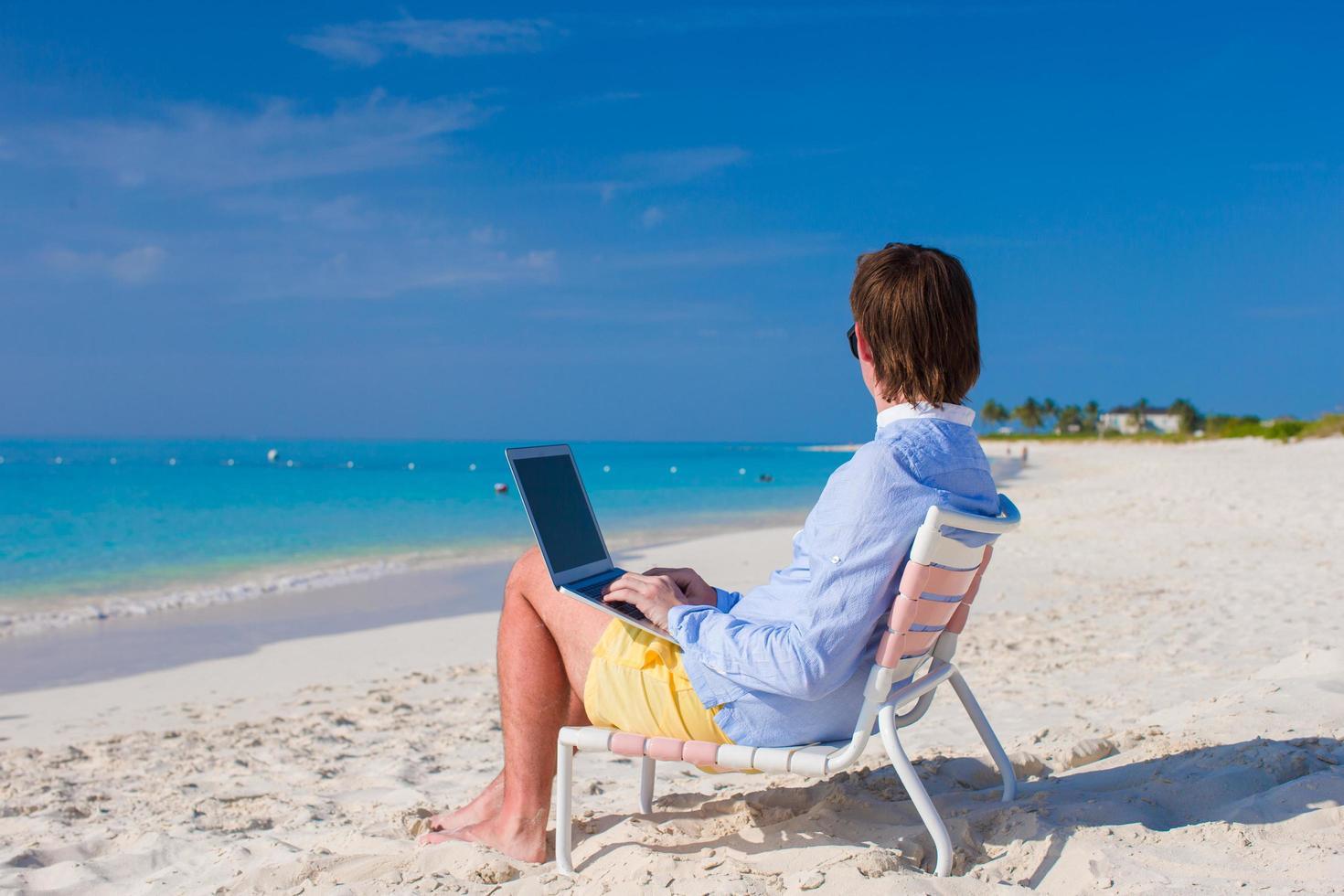 Mann mit einem Laptop an einem tropischen Strand foto