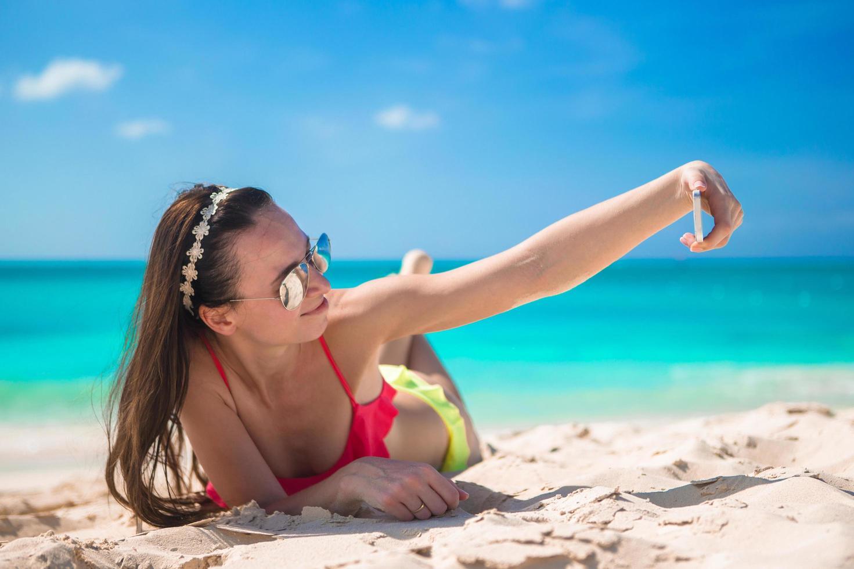 Frau, die ein Selfie am Strand nimmt foto