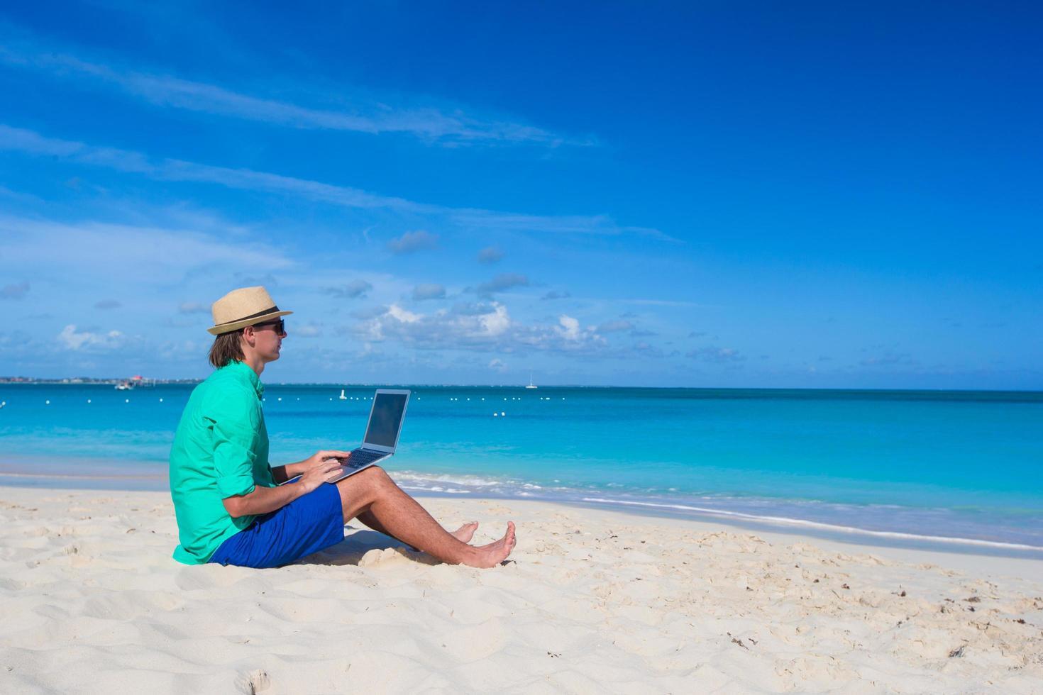 Mann, der an einem Laptop am Strand arbeitet foto