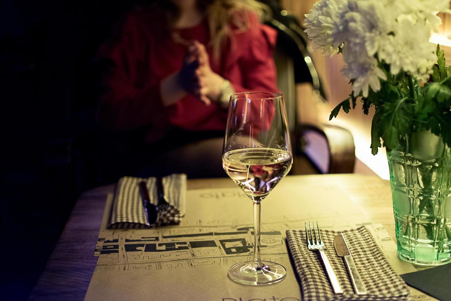 Glas Weißwein auf einem Restauranttisch foto