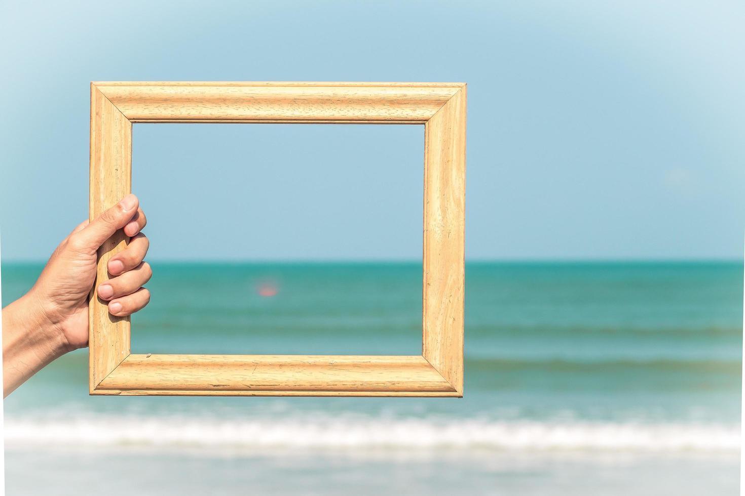 Hand, die Holzrahmen auf Ozeanhintergrund hält foto