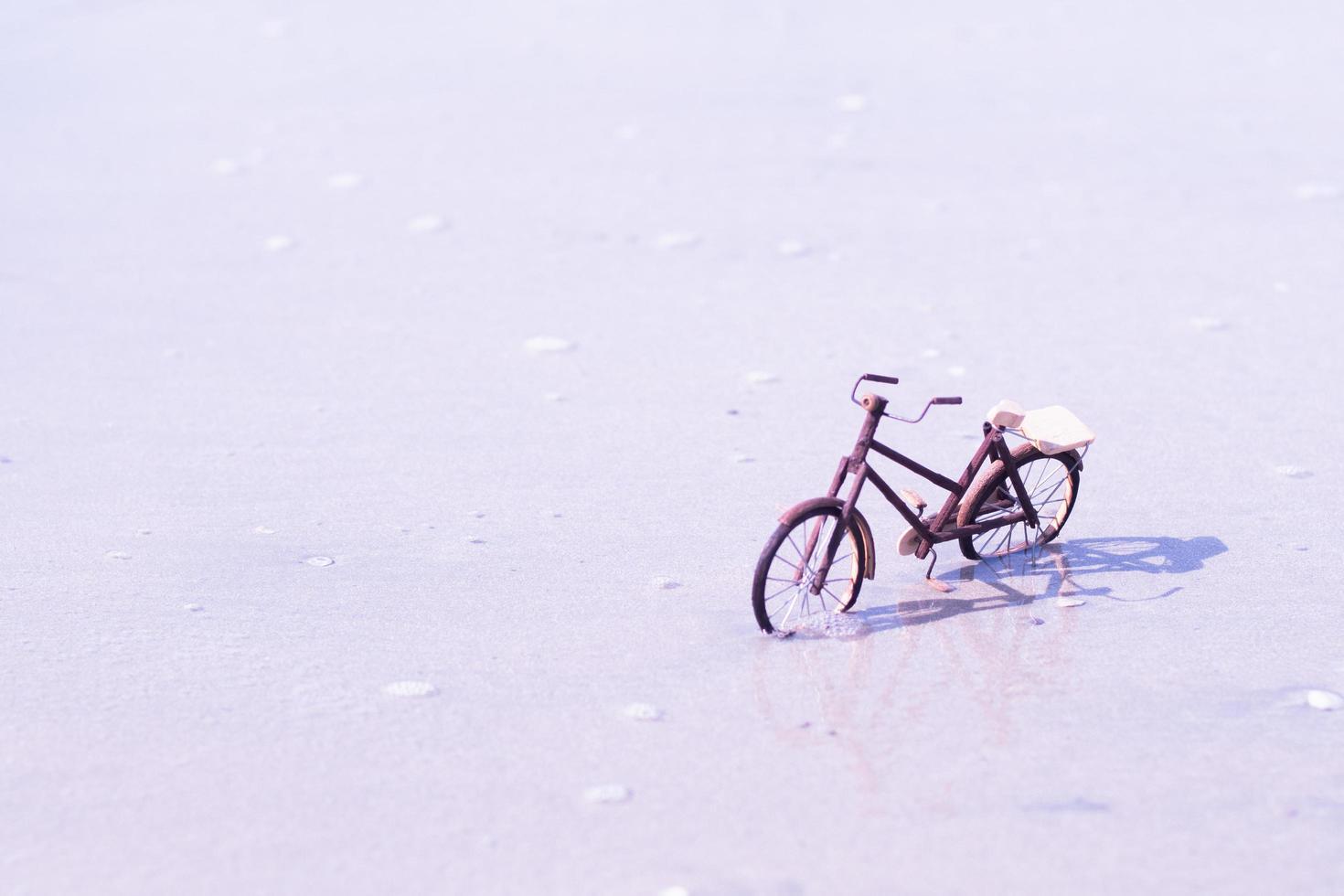 hölzernes Fahrradspielzeug am Strand foto
