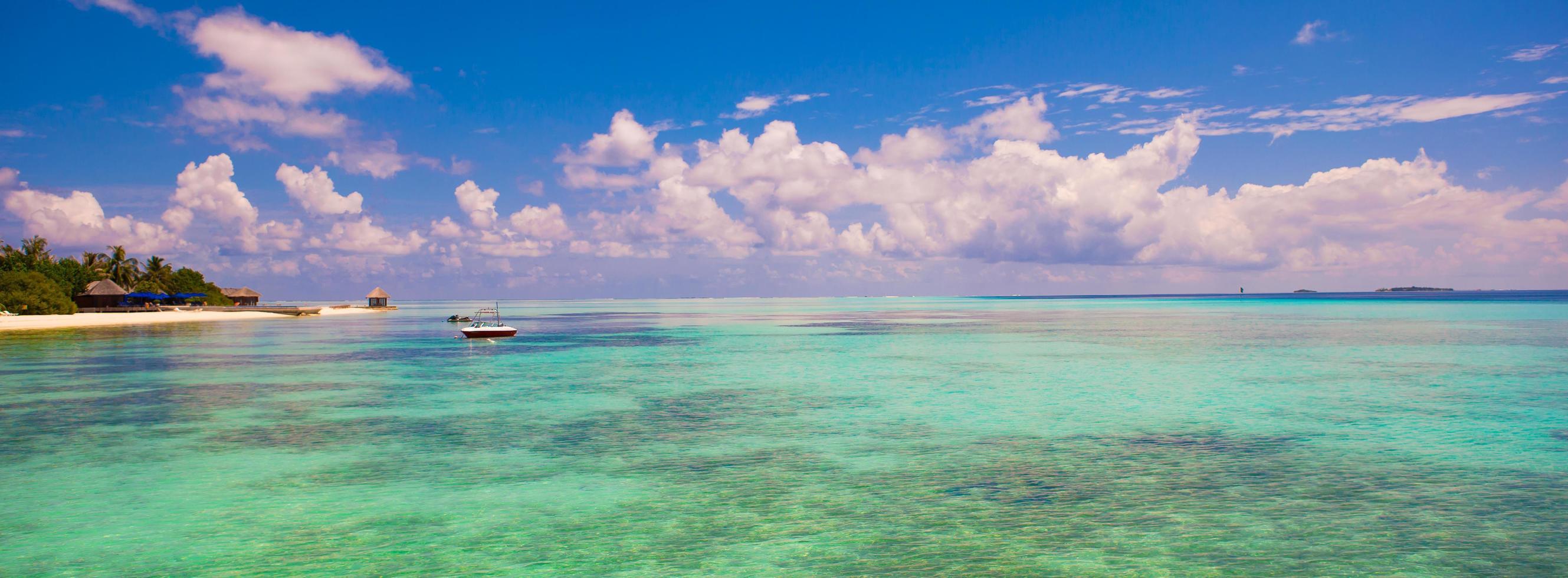 Malediven, Südasien, 2020 - Boot im Wasser in der Nähe eines tropischen Ferienortes foto