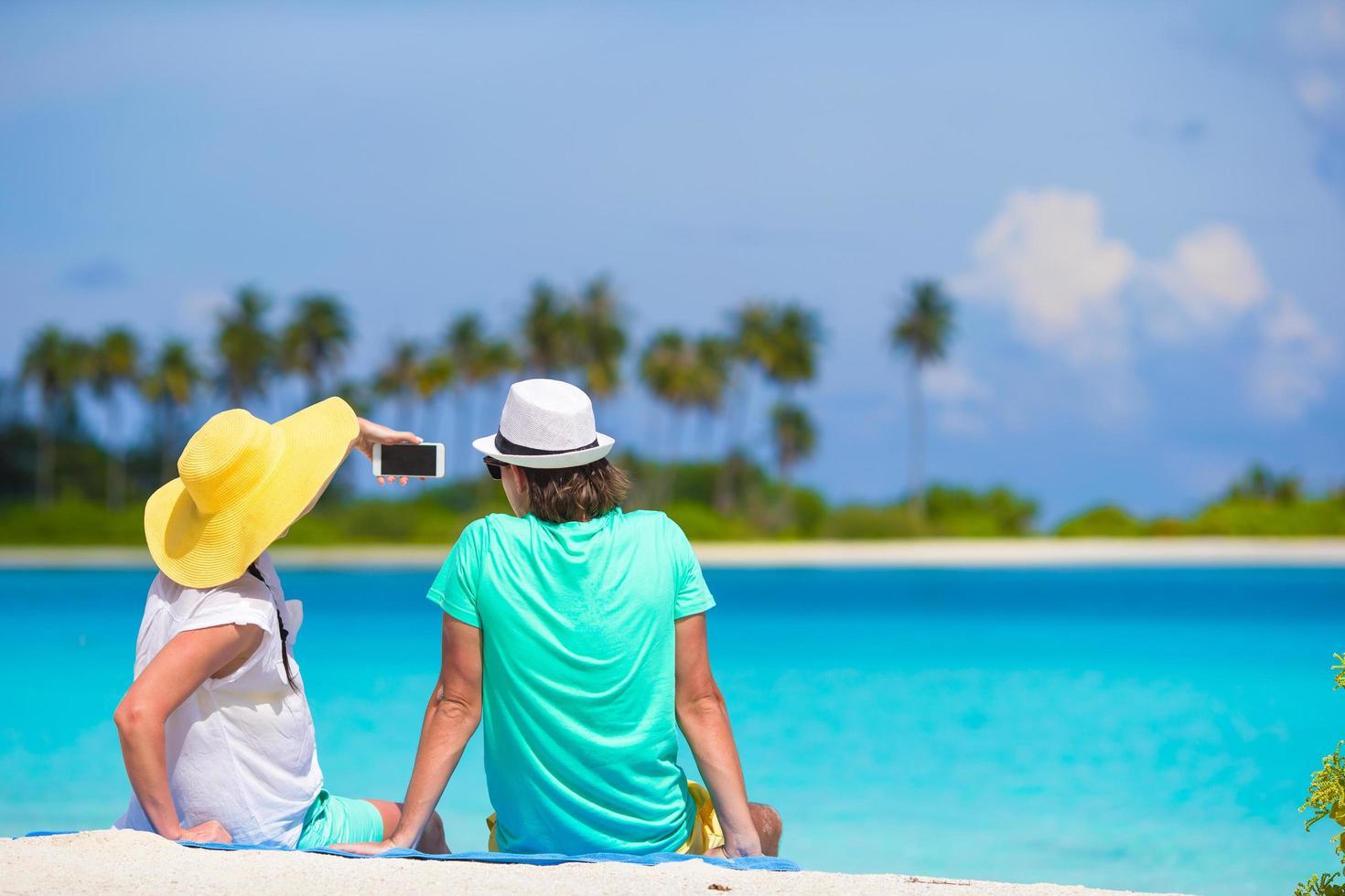 glückliches Paar, das ein Selfie am Strand nimmt foto