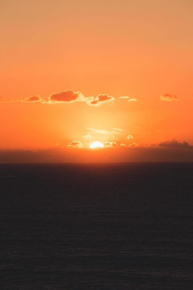 dunkles Land und ein orangefarbener Sonnenuntergang foto