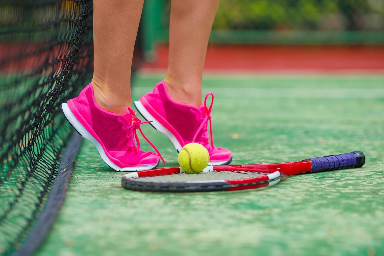 Nahaufnahme von Turnschuhen in der Nähe des Tennisschlägers und des Balls foto