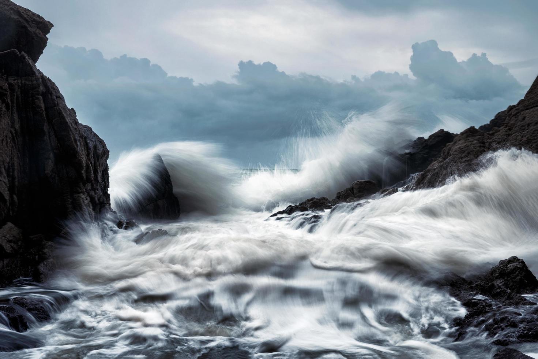 große Welle trifft die Felsen im Sturm foto