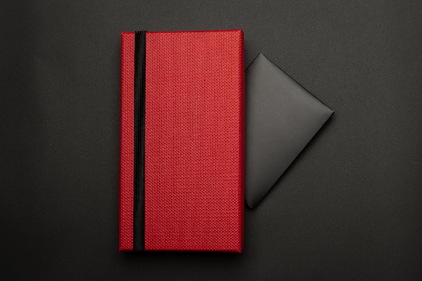 rote Geschenkbox mit schwarzer Umschlagkarte foto