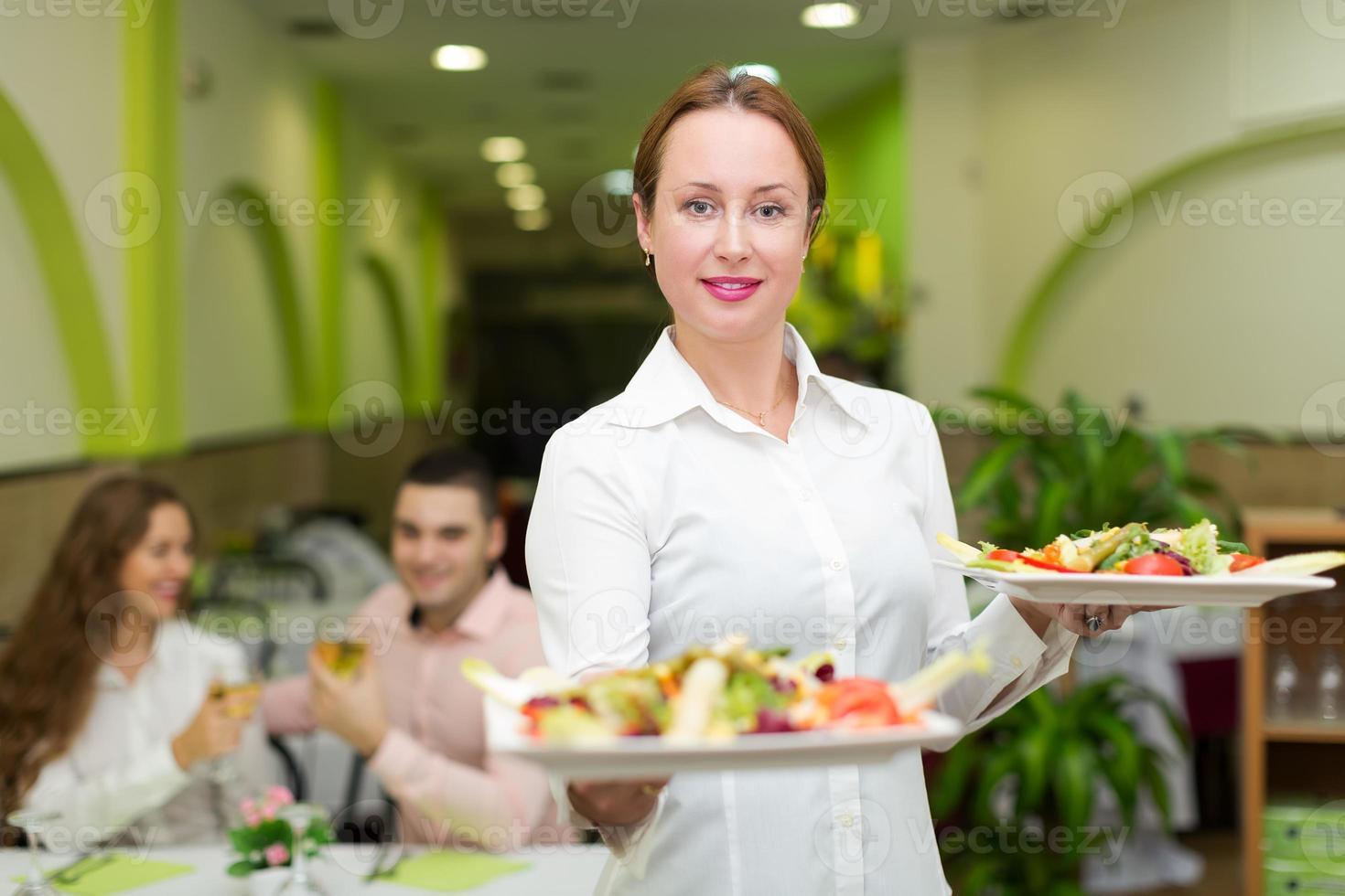 Kellnerin serviert den Besuchern Essen foto