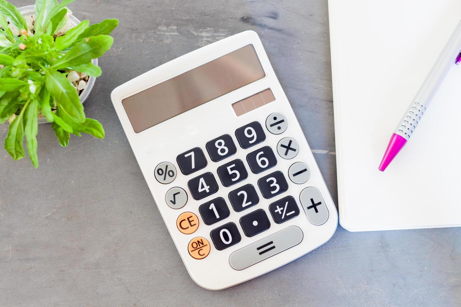 Taschenrechner, Notizblock und Stift mit einer grünen Pflanze foto