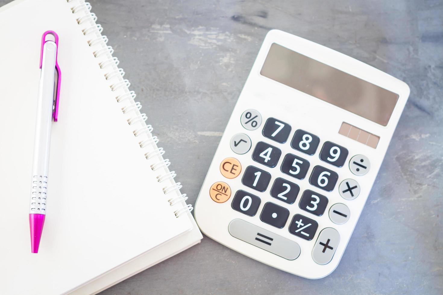 Taschenrechner und Notizblock auf grauem Hintergrund foto