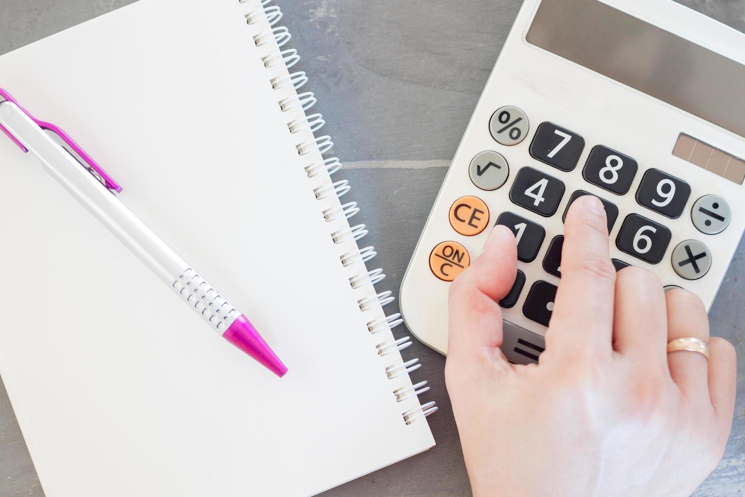 Hand auf einem Taschenrechner mit Notizblock foto