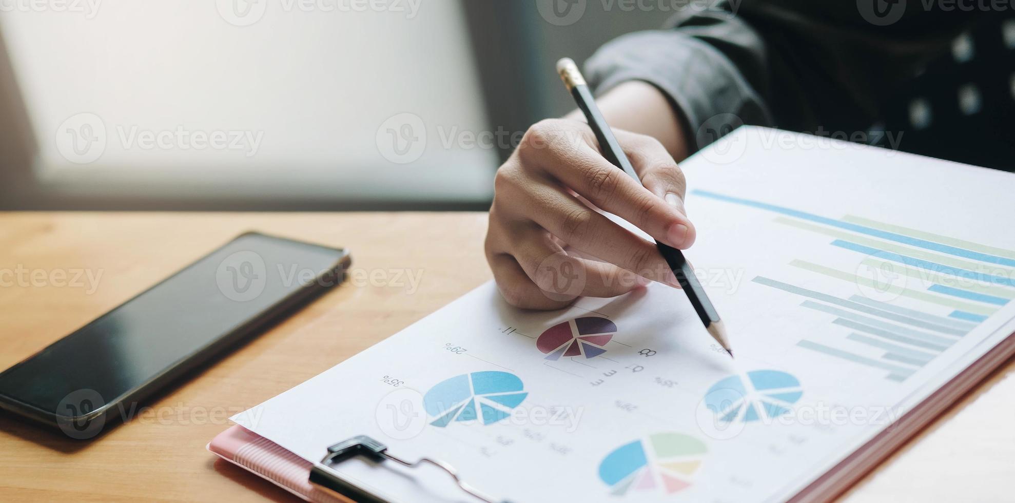 Geschäftsmann, der mit Dokumentengraphen am Schreibtisch arbeitet foto