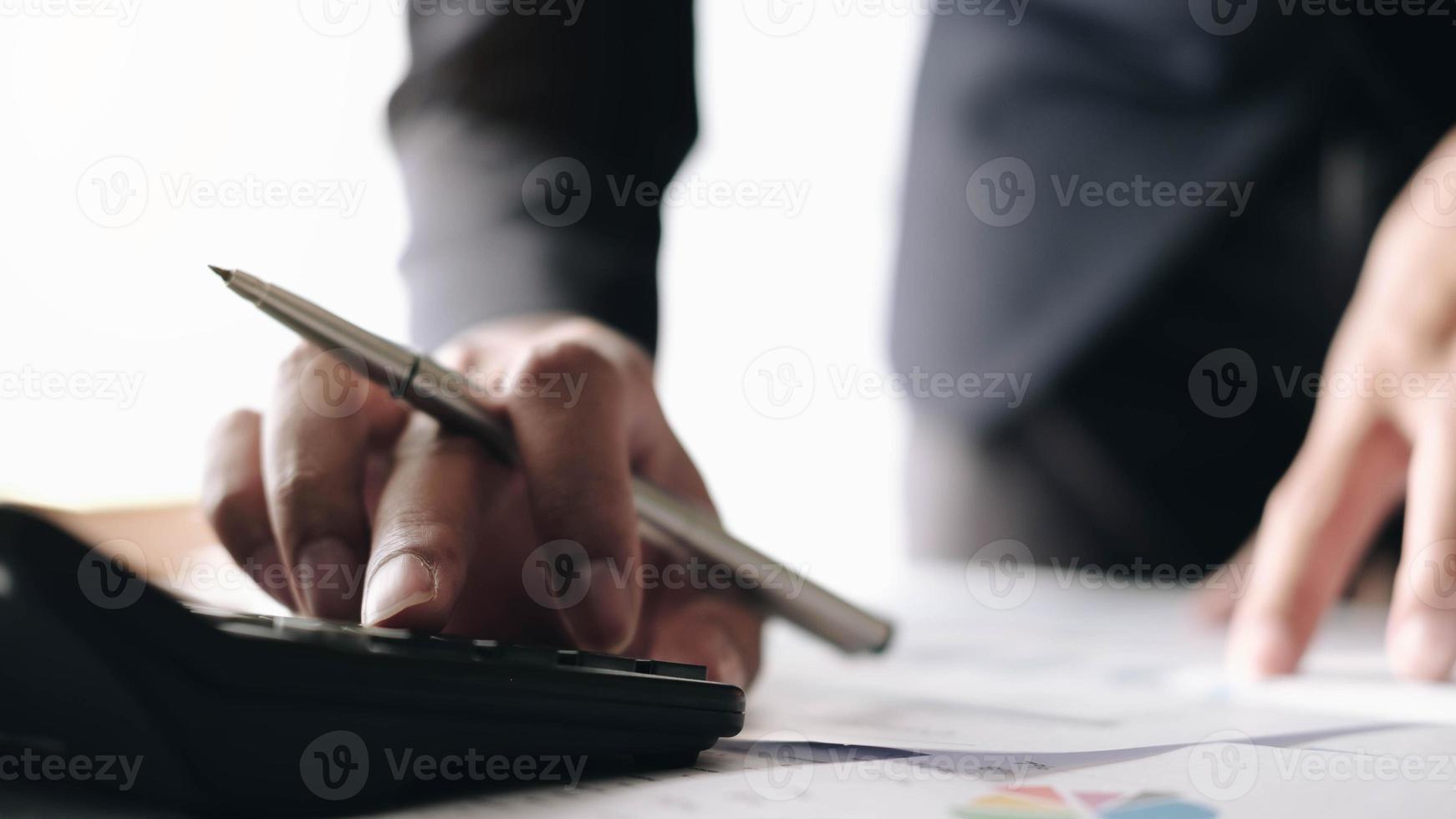 Geschäftsfrau mit Taschenrechner und Laptop am Schreibtisch foto