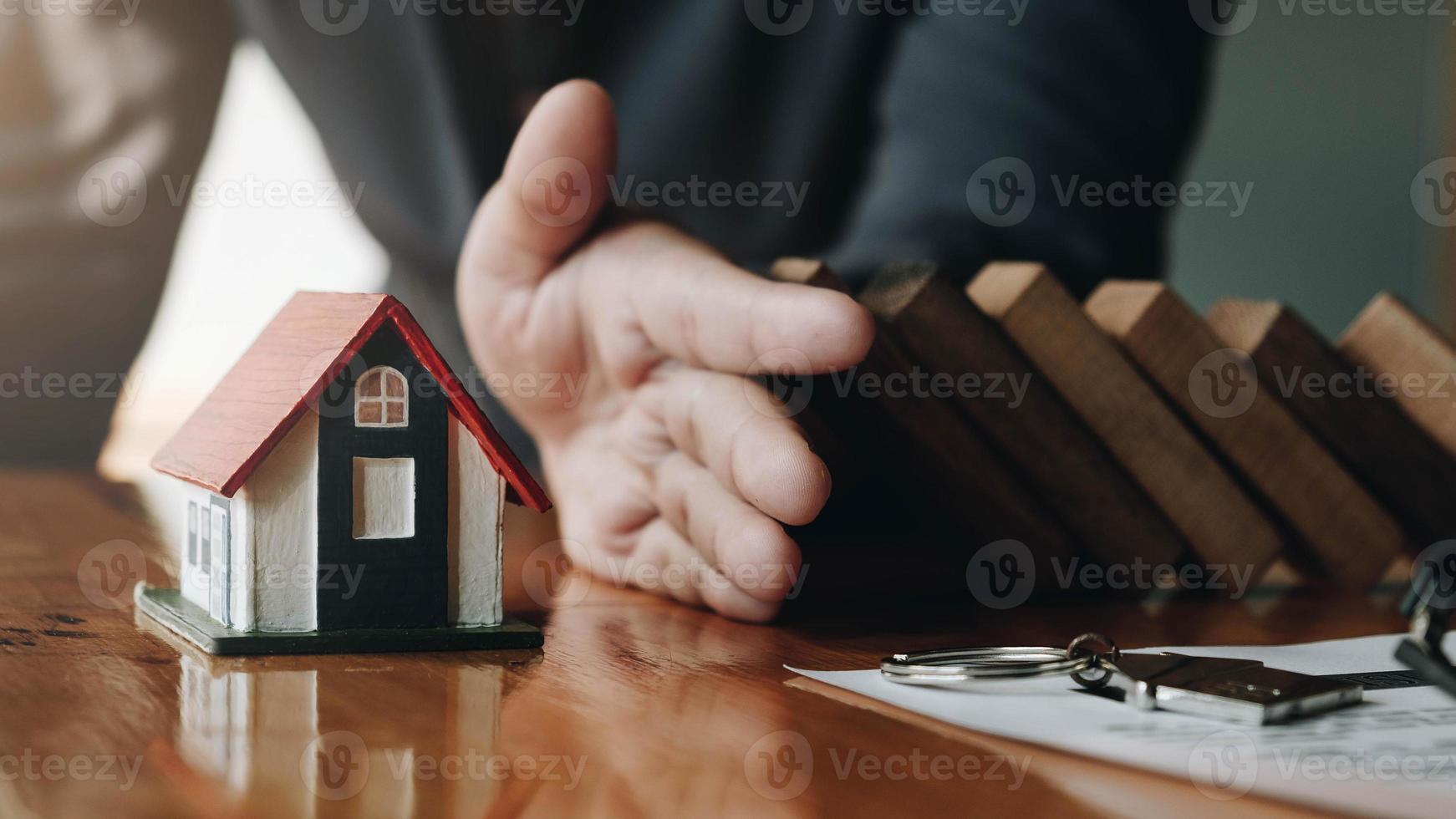 Hand hält Holzklötze für Hausversicherung und Risikokonzept foto