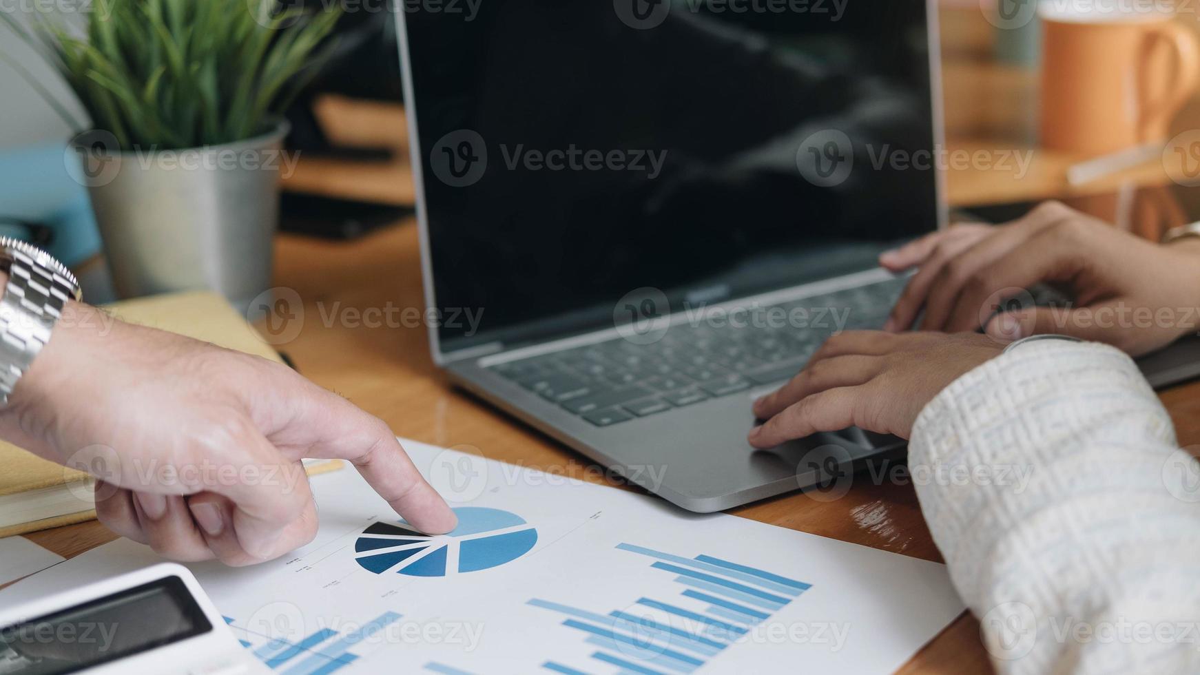 Zwei Geschäftsleute am Schreibtisch besprechen Berechnungen foto