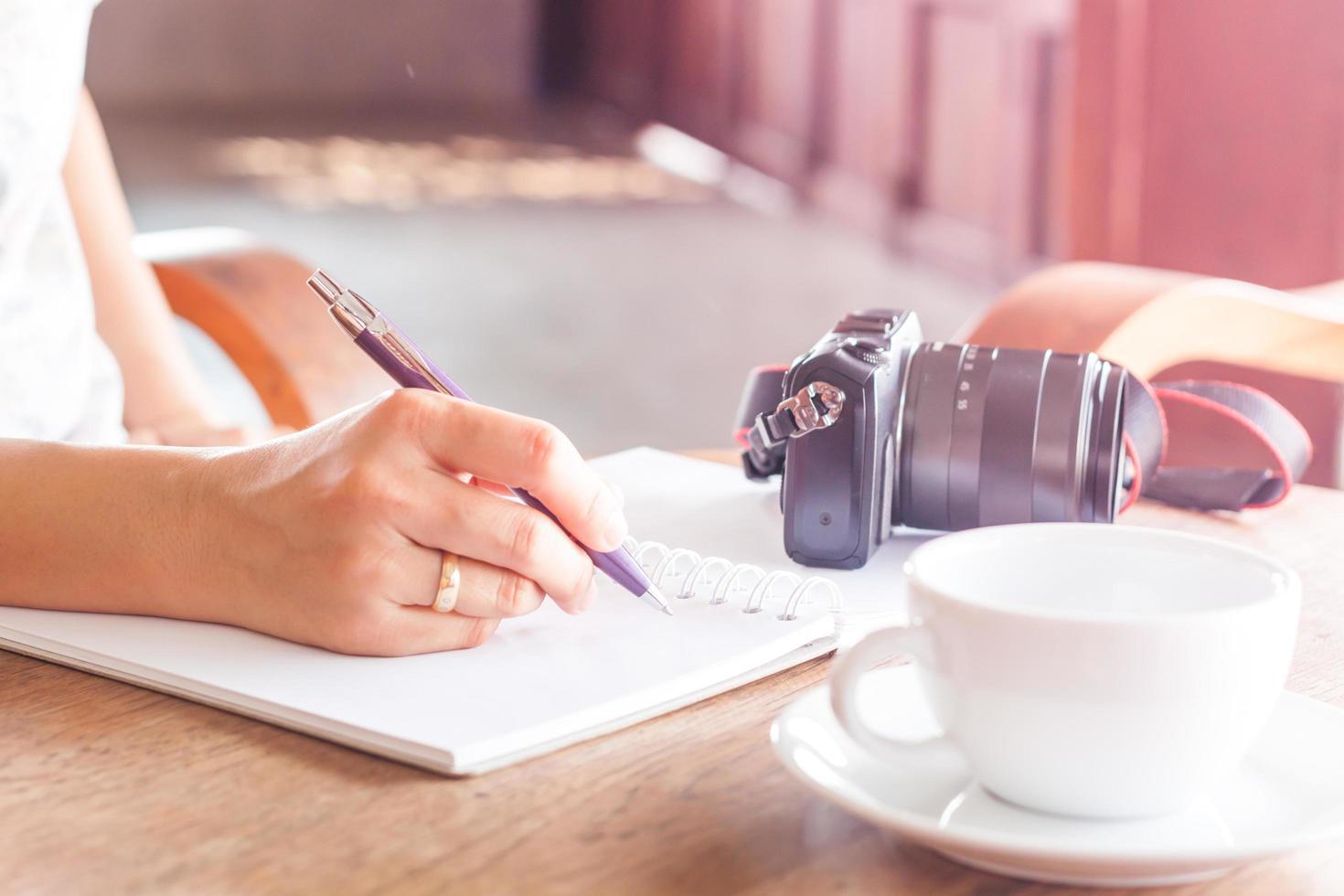 Frau, die in einem Notizbuch mit einer Kamera und Kaffee auf einem Tisch schreibt foto
