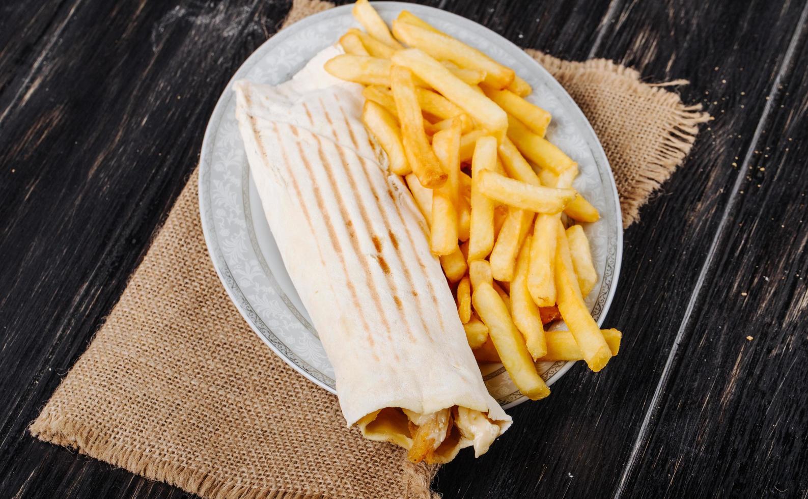 Hühnersandwich mit Pommes Frites auf rustikalem Hintergrund foto