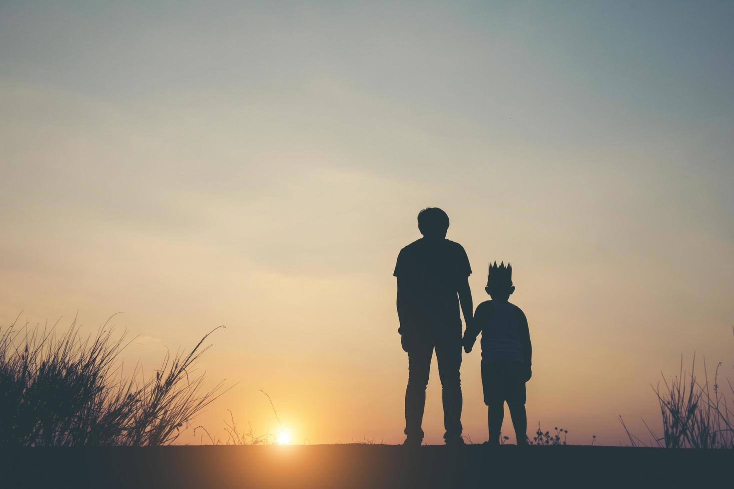 Silhouette von Vater und Sohn zusammen stehend foto