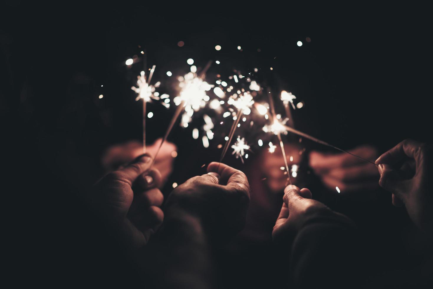 Gruppe von Menschen, die nachts Wunderkerzen halten foto
