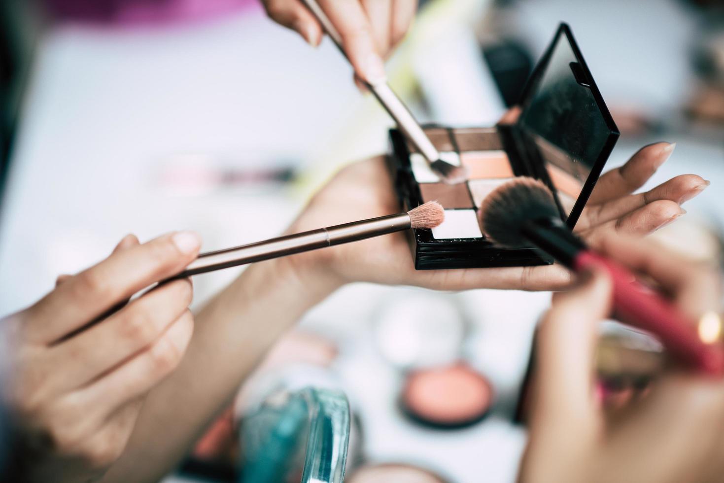 Frauen machen Make-up mit Pinseln und Kosmetikpuder foto
