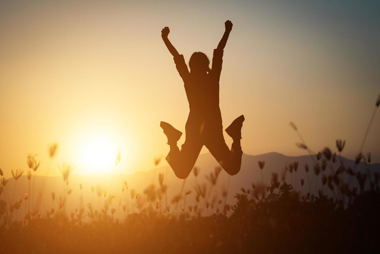 Silhouette einer Frau, die über einen schönen Himmelhintergrund springt foto
