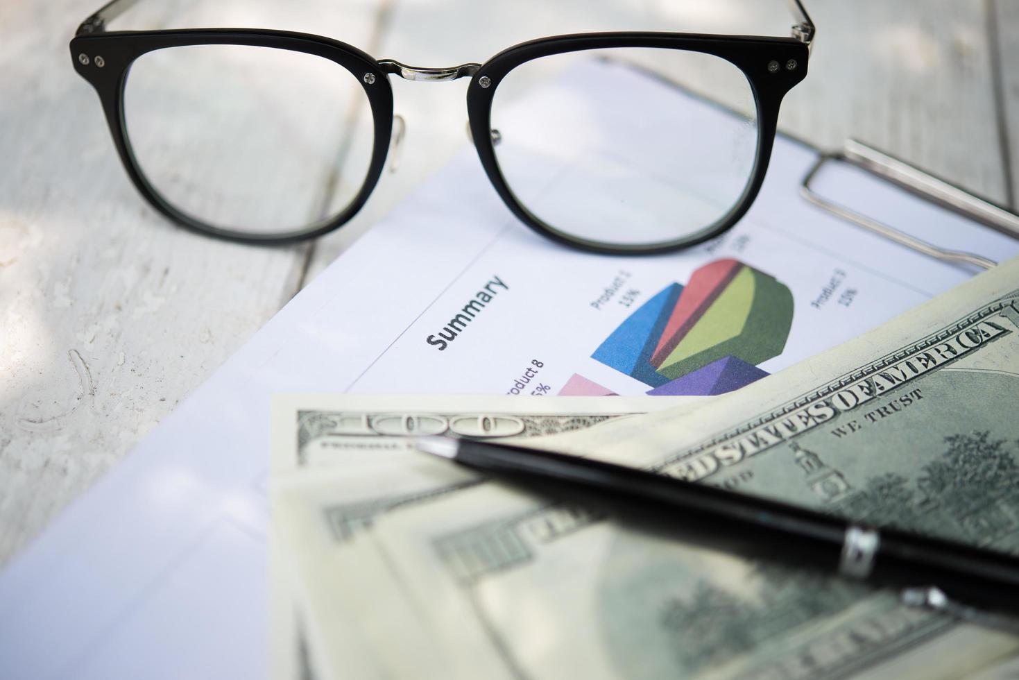 Nahaufnahme des Tisches mit Dokumenten, Brille, Stift und Dollarschein foto