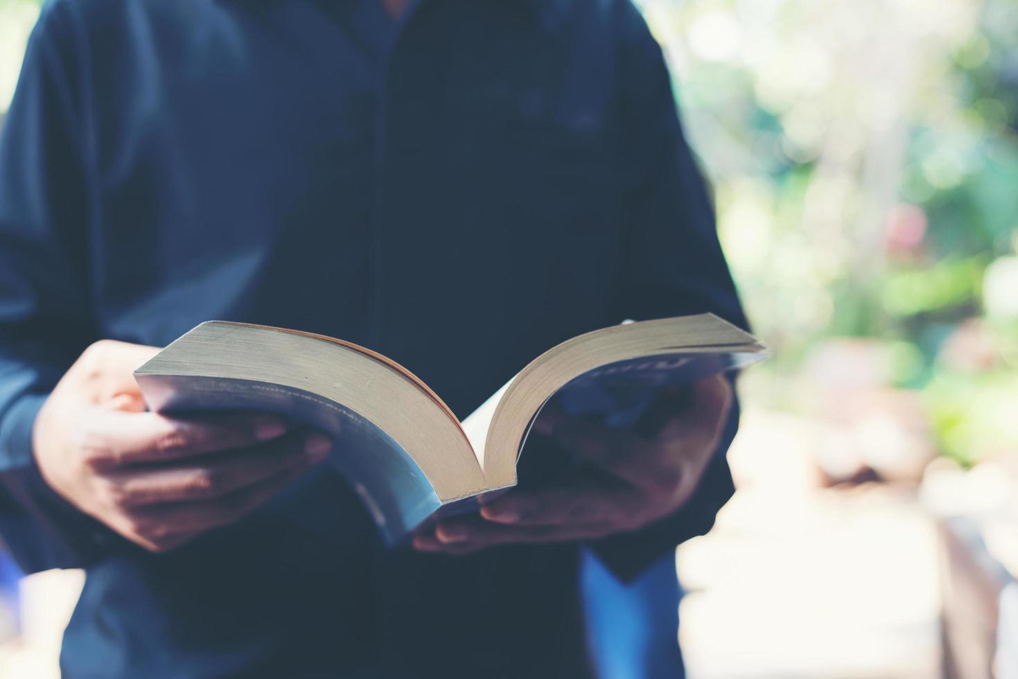Mann liest ein Buch in seinen Händen foto