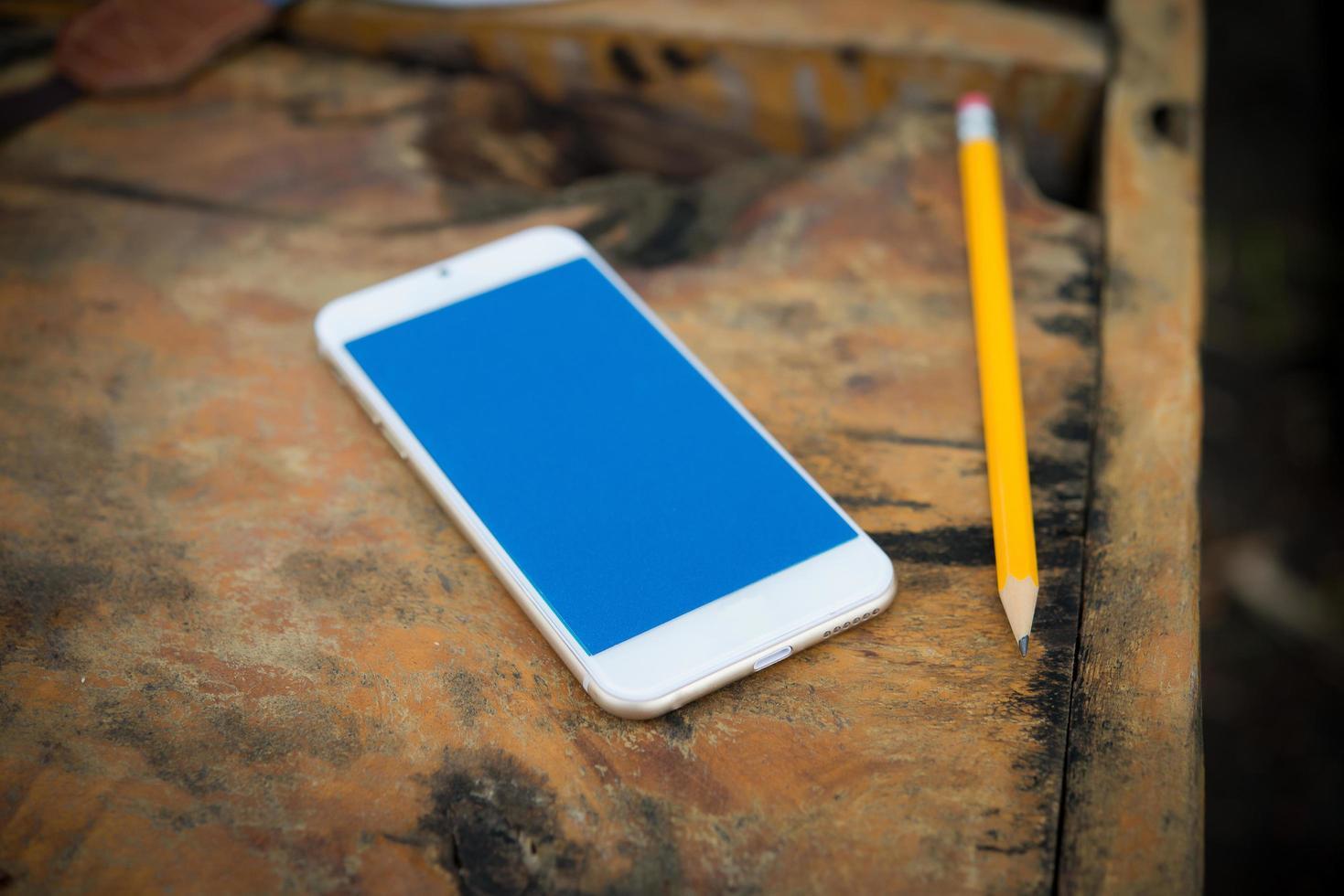 Smartphone mit Bleistift auf einem Holztisch foto