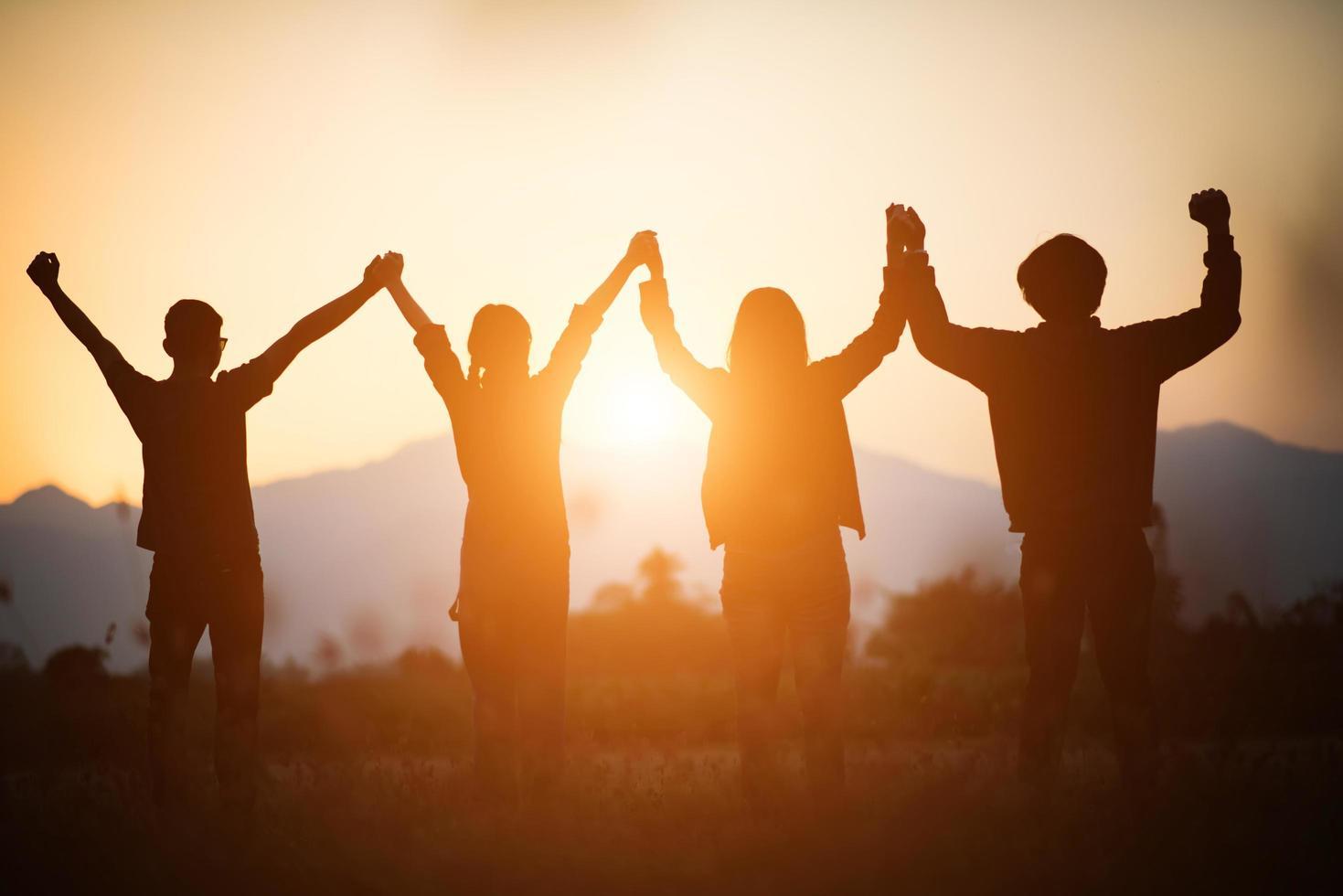 Silhouette des glücklichen Teams, das Hände in der Luft verbindet foto