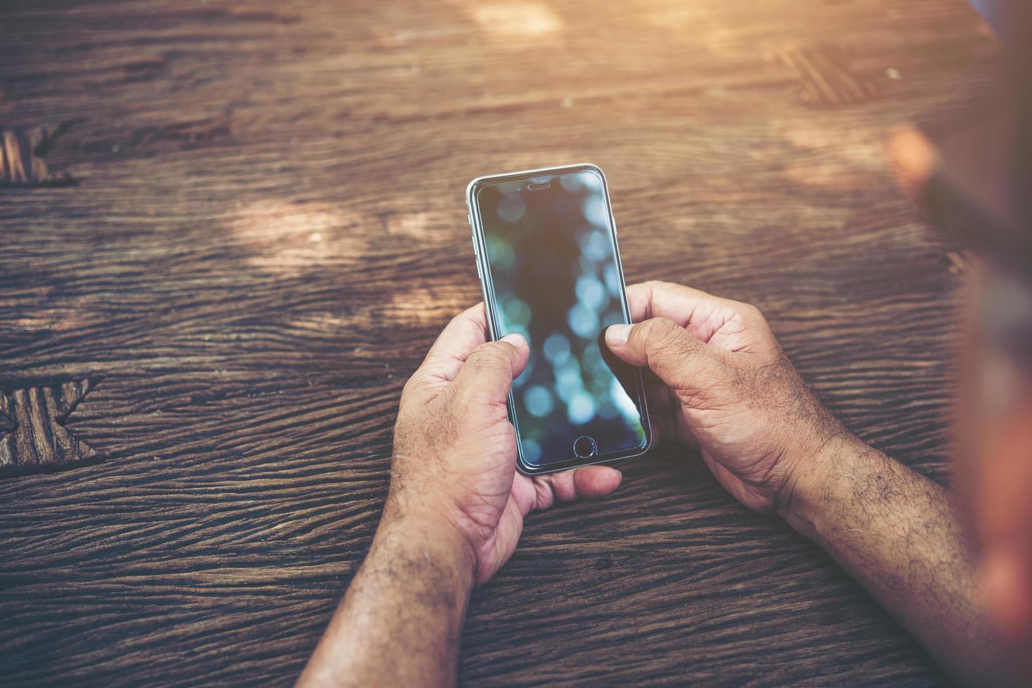 Person, die Smartphone an einem Tisch hält foto