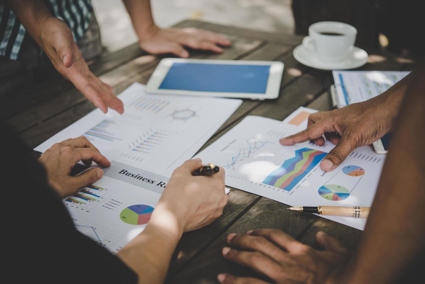 Eine Gruppe von Geschäftsleuten analysiert Diagramme bei Besprechungen foto